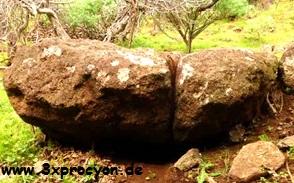 Ein teilweise unterhöhlter Felsbrocken mit einer breiten Spalte im Hang.